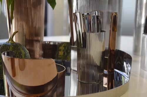Kokoelmassa käytetty juhlava pystyraidoitus vie ajatukset Sigvard Bernadotten Georg Jensenille suunnittelemiin aterimiin. Ruusukullan värinen PVD-pinnoite luo kontrastia ja lisää kattaukseen elävyyttä.