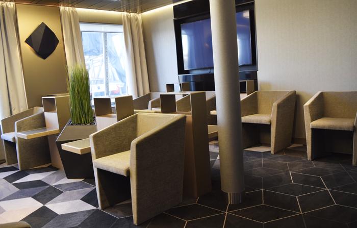 Business Loungessa on useita erilaisia tilaratkaisuja. Tässä nurkkauksessa kalusteet keskustelevat hauskasti lattiamaton kuvioinnin ja isoista ikkunoista siivilöityvän auringonvalon kanssa.